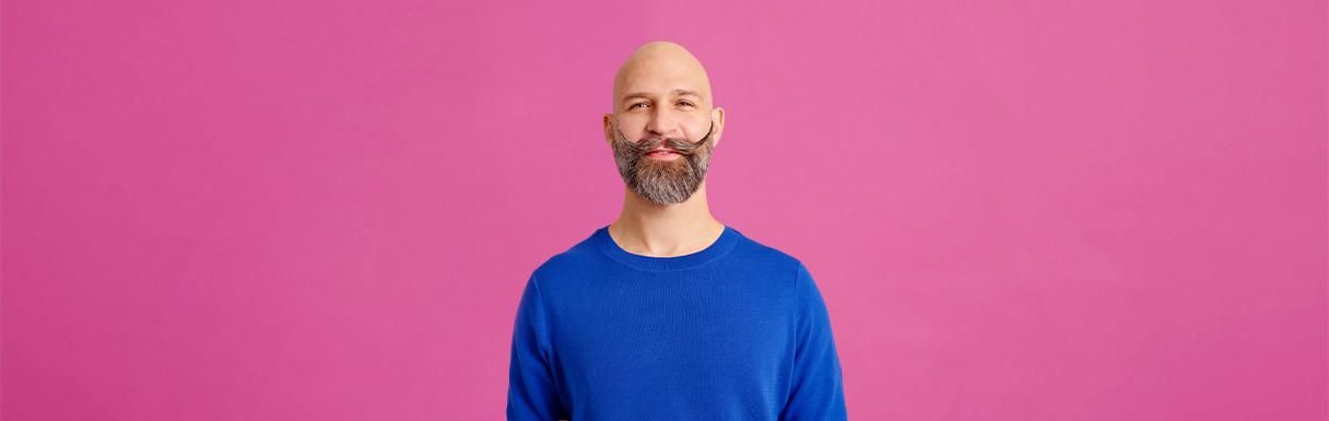 Manlig patient hos Folktandvården som är glad och har en rolig mustasch.