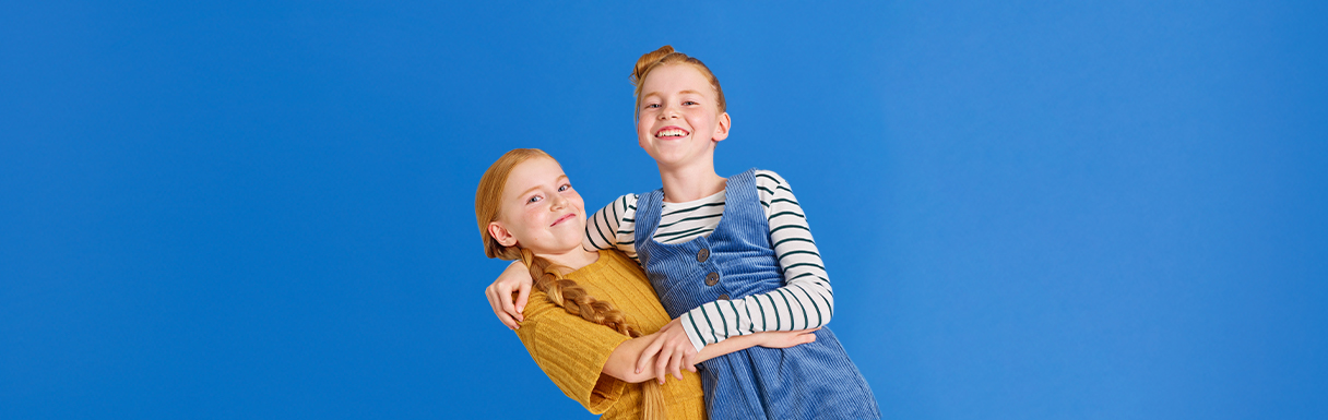 Två flickor som har sin tandläkaren på Folktandvården håller om varandra och skrattar.